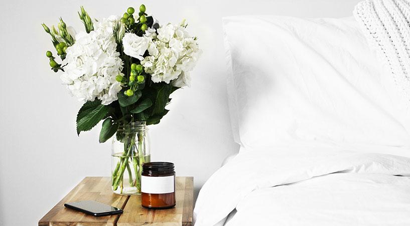 Vase mit grünen Blumen neben dem Bett