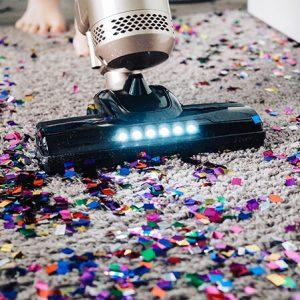 Buntes Konfetti wird mit einem Staubsauger vom Teppich entfernt
