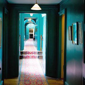 Langer Flur mit grünen Wänden und Läufer mit Muster