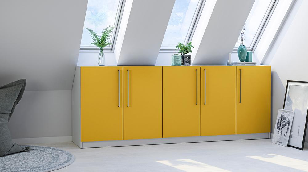Kommode mit gelben Fronten unter einer Dachschräge mit Fenstern