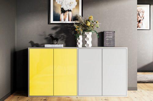 Grau Kommode mit zweifarbigen Fronten in grau und gelb vor einer Wand